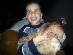 A boy cuddling a cockerel